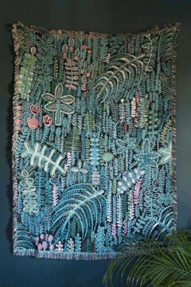 lifestyle image of Lucy Tiffney Vibrant Lagoon Cotton Throw hanging on dark grey wall with house plant in corner