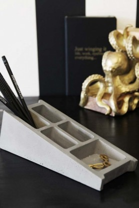 lifestyle image of Lyon Beton Concrete Desk Organiser with jewellery and pencils in on black table with gold octopus ornament and black notebook