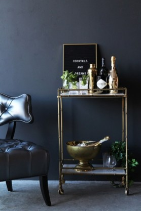 lifestyle image of Makrana Marble Drinks Trolley with black message board and gold drink accessories with metallic pewter cloud chair and dark wall background