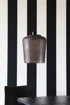lifestyle image of Martina Smoked Glass Pendant Light above black table and chair with black and white striped wall background
