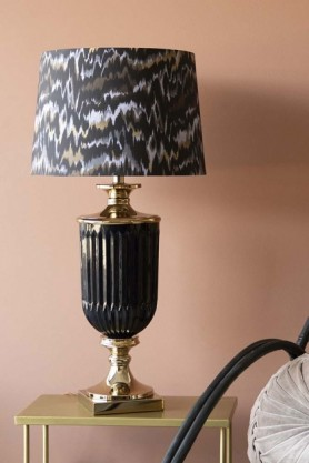 lifestyle image of the Matthew Williamson Hyde Park Table Lamp & Animal Print Shade in gold side table with pale coloured wall background