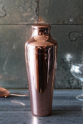 lifestyle image of Mercer Copper Cocktail Shaker on grey table with glass behind and tiled wallpaper background