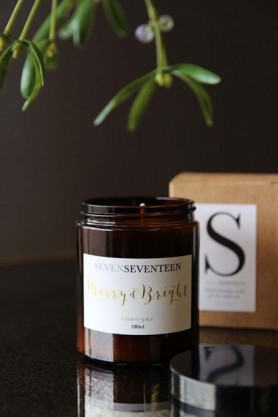 lifestyle image of Merry & Bright Winter Spice Candle with box and mistletoe on black table
