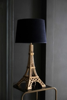 lifestyle image of Metal Eiffel Tower Table Lamp with dark blue shade on gold side table and grey wall background