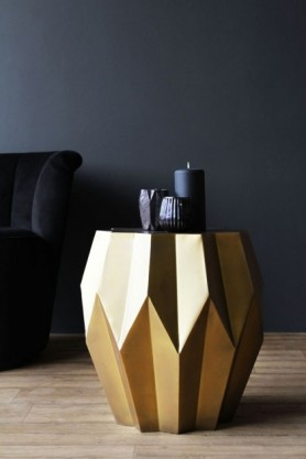 lifestyle image of Midas Gold Geometric Side Table with black candles on top and black armchair on wooden flooring and dark wall background
