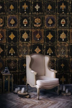 Lifestyle image of the dark shade of Anna's Jewellery wallpaper with white armchair in front of it and candles on wooden stumps on floor