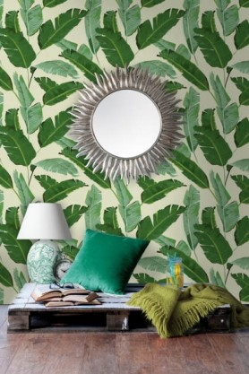lifestyle image of Mind The Gap Banana Leaves Wallpaper with wooden pallet and table lamp with green cushion and blanket with mirror on wall