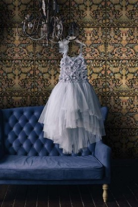Lifestyle image of the anthracite Brocade wallpaper with blue sofa and purple dress hanging from a chandelier in front of it