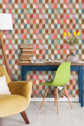 Lifestyle image of Mind The Gap Coloured Geometry Wallpaper with blue desk and green chair in front and yellow armchair in foreground