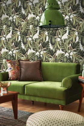 lifestyle image of Mind The Gap Exotic Fruit I Wallpaper with green ceiling light and green sofa with grey cushion and wooden coffee table