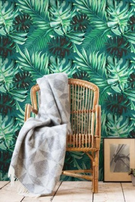 lifestyle image of Mind The Gap Rainforest Wallpaper with rattan chair and grey blanket with picture frame on pale wooden flooring