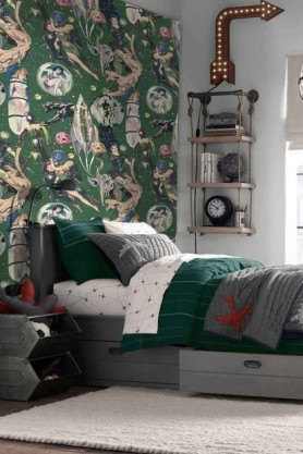 lifestyle image of Mind The Gap Sci-Fi Comics Wallpaper in child bedroom with green bedding on bed and white rug with industrial style shelving unit on wall