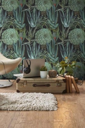 lifestyle image of Mind The Gap The Rediscovered Paradise - Succulentus Wallpaper - Anthracite with wooden suitcase and laptop with plants and rug on floor