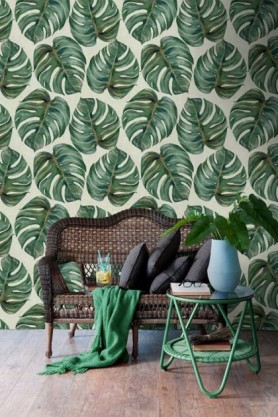 lifestyle image of Mind The Gap Tropical Leaf Wallpaper with wooden bench with green blanket and grey cushions and green side table with plant on top