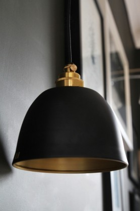 lifestyle image of Miniature Bell Brushed Brass & Dusky Matte Black Ceiling Light with picture frames hung on dark wall background