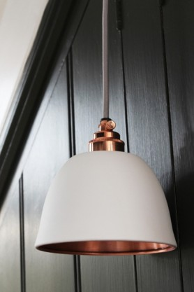 lifestyle image of Miniature Bell Copper & Matte White Ceiling Light with paneled dark grey wall background