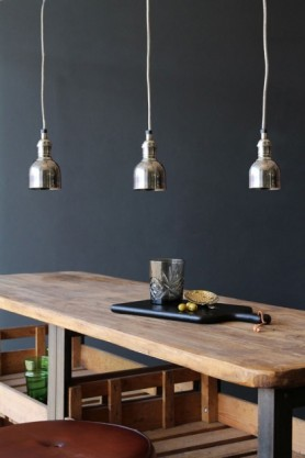 Lifestyle image of three Miniature Bell Industrial Ceiling Light's over wooden dining table with dark grey wall background