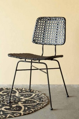 Lifestyle image of the black Modern Woven Rattan Dining Chair facing forwards with mandala rug and grey flooring on pale wall background