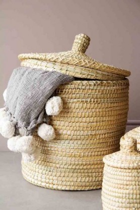 lifestyle image of Large Moroccan Wicker Basket with throw hanging out and lid slightly off with small basket in foreground and grey flooring and pale wall background