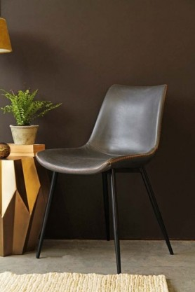 lifestyle image of Morris Faux Leather Dining Chair - Charcoal Grey with gold side table with plant on top and beige rug and dark brown wall background