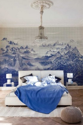 Lifestyle image of the Mountains Wallpaper Mural - Kami Blue Spirulina in bedroom with white double bed with blue bedding and two side tables with white table lamps on top