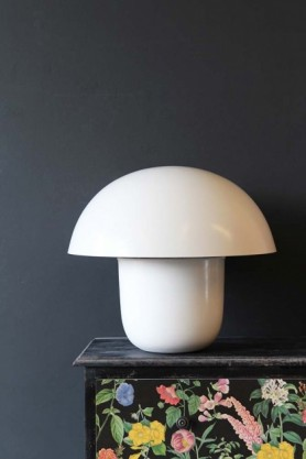 lifestyle image of Mushroom Table Lamp - Ivory on patterned black table and grey wall background