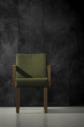 lifestyle image of NLXL CON-07 Concrete Wallpaper by Piet Boon with green armchair on grey flooring
