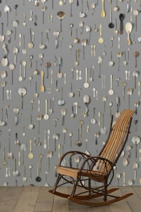 lifestyle image of NLXL DRO-06 Obsession Small Spoons Wallpaper by Daniel Rozensztroch with black and brown rocking chair