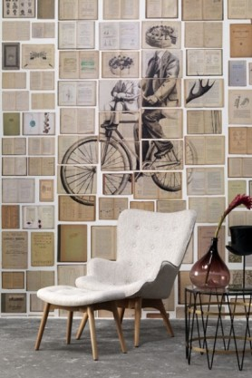lifestyle image of NLXL EKA03 Biblioteca Wallpaper by Ekaterina Panikanova - Mural 3: Bicycle with white armchair and foot stool and metal side table with brown vase