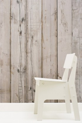 lifestyle image of NLXL PHE-07 Scrapwood Wallpaper by Piet Hein Eek with side view of white wooden chair