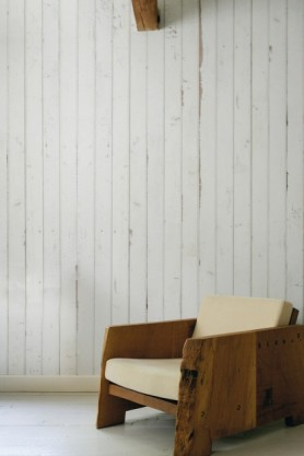 lifestyle image of NLXL PHE-08 Scrapwood Wallpaper by Piet Hein Eek with cream and wooden armchair