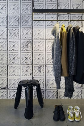 lifestyle image of NLXL TIN-04 Brooklyn Tin Tiles Wallpaper By Merci with black stool and black clothing rack with clothes on and trainers underneath