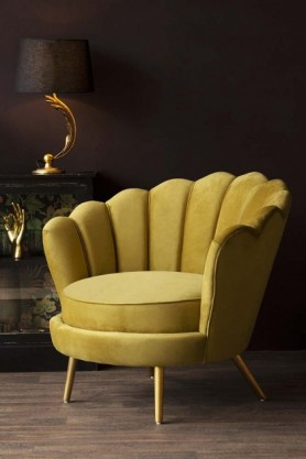 Lifestyle image of the Ochre Gold Velvet Petal Occasional Chair with cabinet and table lamp in background with dark wall background and wooden flooring