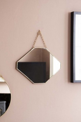 Lifestyle image of the Octagon Gold Hanging Bathroom Mirror hanging on pale wall with round mirror and picture frame