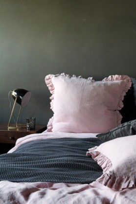 lifestyle image of Olivia Soft Linen Frill Cushion - Rose Pink on bed with pink duvet and grey bedding and wooden side table with metal table lamp and grey wall background