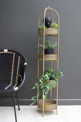 lifestyle image of Ornate Gold Tall Tray Shelves with plant on each shelf and black rattan chair on white flooring and grey wall background