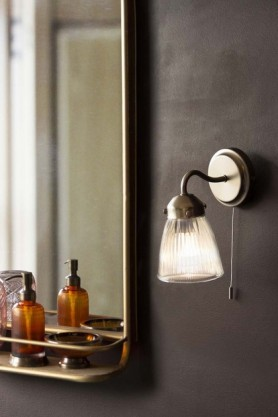 lifestyle image of Pimlico Bathroom Wall Light in Satin Nickel lit up with Light Gold Tall Bathroom Mirror With Shelf and apothecary style soap dispenser on dark wall background