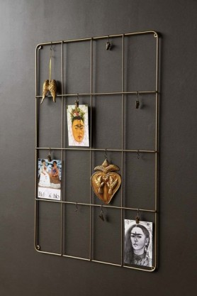 lifestyle image of Rectangular Brass Wall Frame with picture pegged on and dark wall background