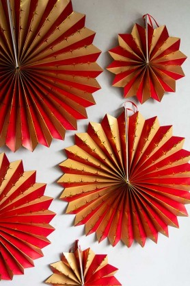 Close-up lifestyle image of the Pack Of 5 Assorted Sized Carnival Paper Fans hanging on the wall
