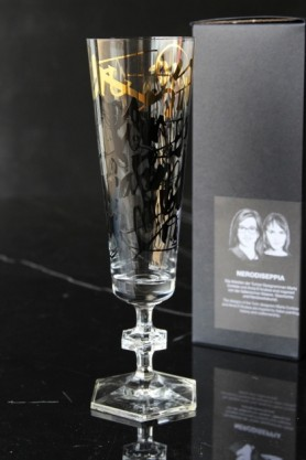 lifestyle image of Ritzenhoff Champagne Flute - Nerodiseppia with black and gold messy writing on and box in background on black table