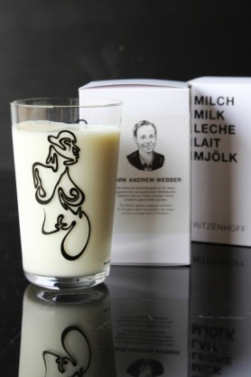 lifestyle image of Ritzenhoff Milk Glass - Mark Andrew Webber with black naked woman drawing on with milk in and box in background on black table
