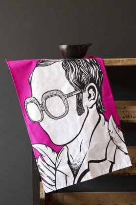 Lifestyle Image of the Elton John Tea Towel hanging from distressed wooden unit on a dark wall background