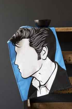 Lifestyle image of the Elvis Presley Tea Towel hanging off a distressed wooden cabinet on a dark wall background