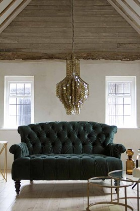 Lifestyle image of the Two-Seater Forest Green Velvet Sofa and Set Of 2 Circular Circus Nesting Tables and Shimmering Shell Disc Chandelier