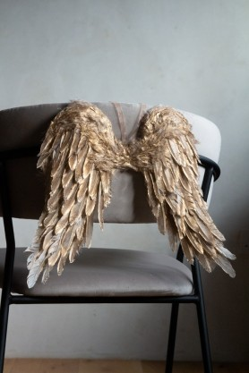 Image of the Gold Feather Wings Hanging Decoration hanging on the back of a chair