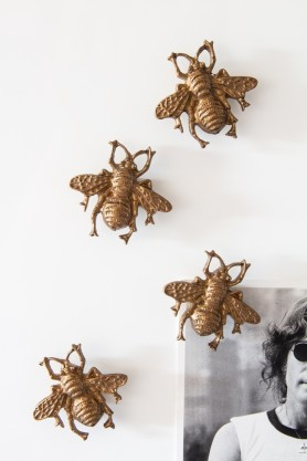 Image of the Set Of 4 Gold Bee Magnets with one corner of a picture pinned to the fridge