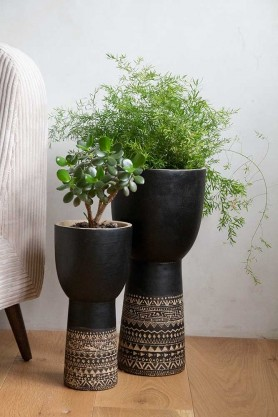 Lifestyle image of the both sizes of the Black & Natural Aztec Design Plant Pot with faux plants in them