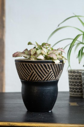 Lifestyle image of the Black & Natural Chevron Pattern Flower Pot with faux plant inside