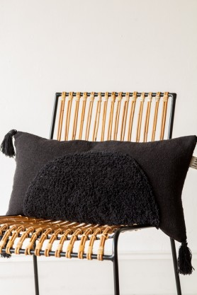 Image of the Black Multi-Texture Cushion With Tassels on a chair