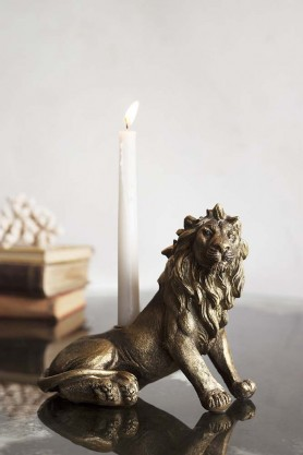 Lifestyle image of the Majestic Lion Resting Candle Holder with a candle in the holder